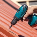 Worker on a roof with electric drill installing red metal tile o